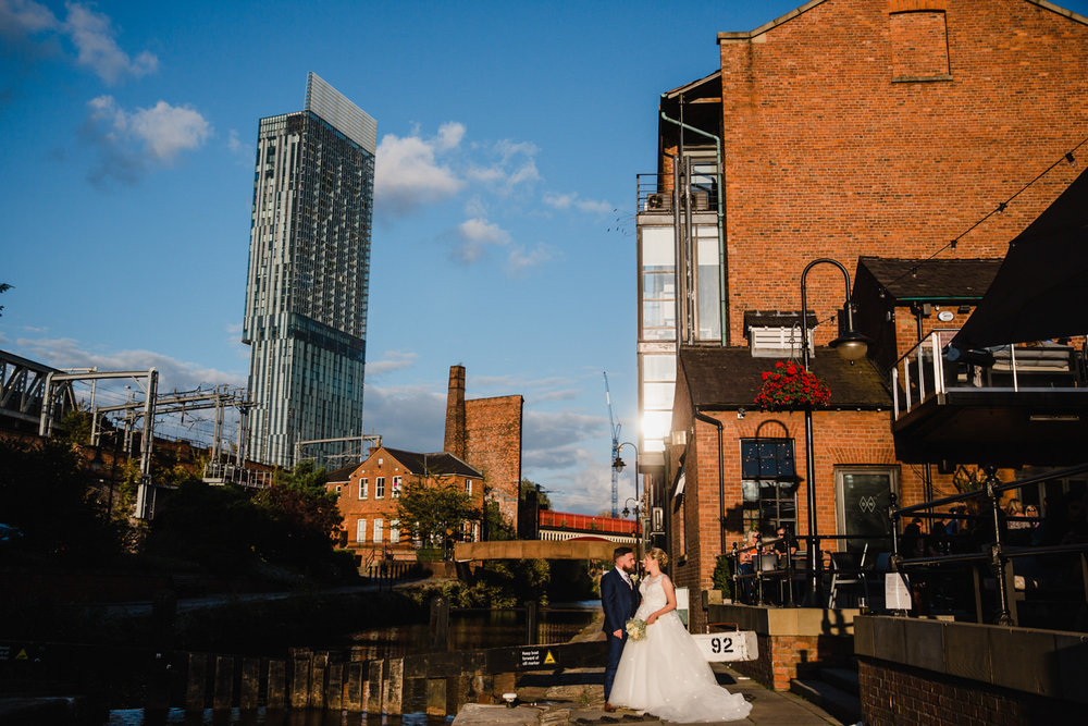 Wide Angle photograph of bride and groom at Castlefield Rooms Lock 92 and Dukes 92 in the background