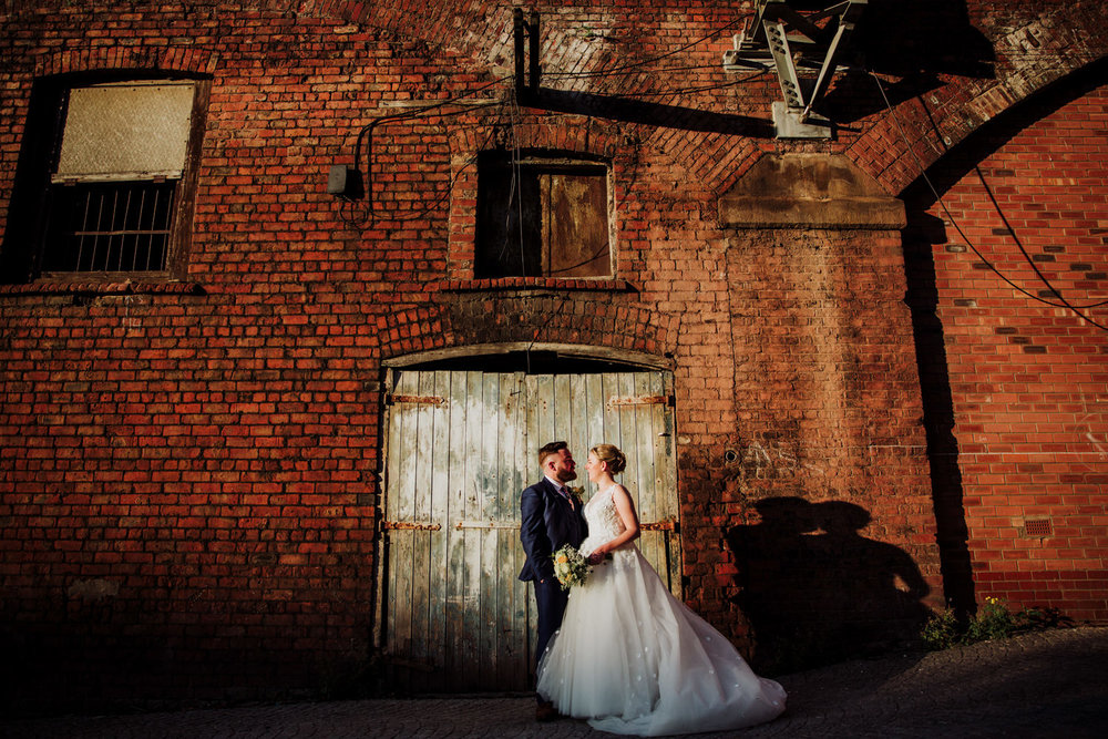 bride and groom in front of blue wooden doorway for a portrait at the castlefield rooms