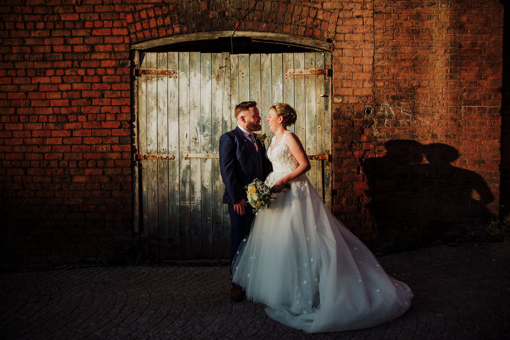bride and groom in front of blue wooden doorway as a close up portrait in front of the castlefield rooms