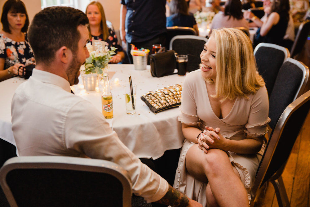 wedding guests sat at table laughing and joking