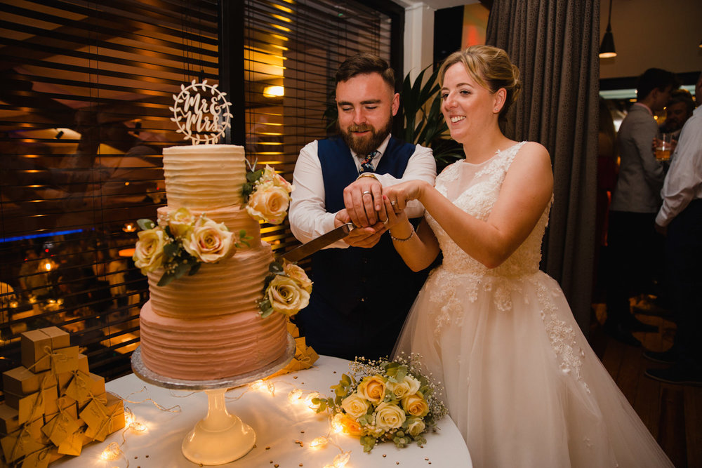 bride and groom cutting the cake together at their castlefield wedding