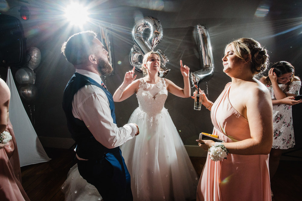 bride dancing with bridesmaid and partner in front of silver balloons and celebration bunting