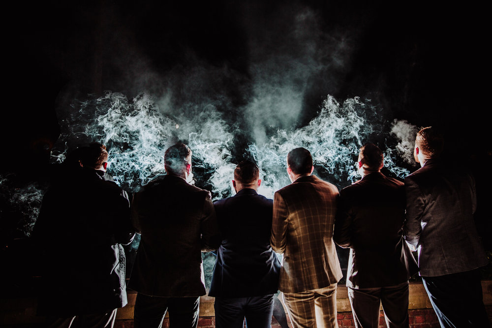 groom and groomsmen outside from wedding as they smoke cigars together with smoke lit up by light at the castlefield rooms in deansgate