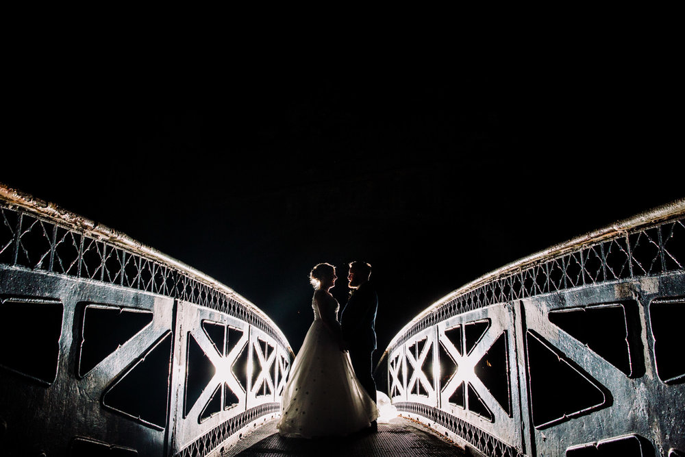 off camera flash lit wide angle silhouette photograph of bride and groom on bridge at the castlefield rooms