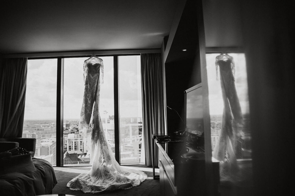 pronovias wedding dress hung up against window in hilton hotel deansgate