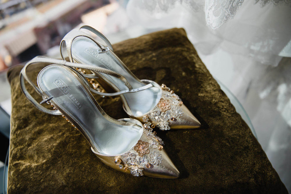 brides golden sequinned wedding shoes sitting on cushion next to window