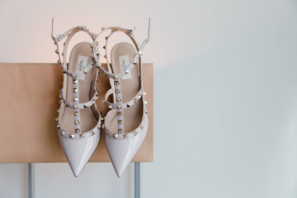 valentino wedding shoes hung up against lamp shade on wall