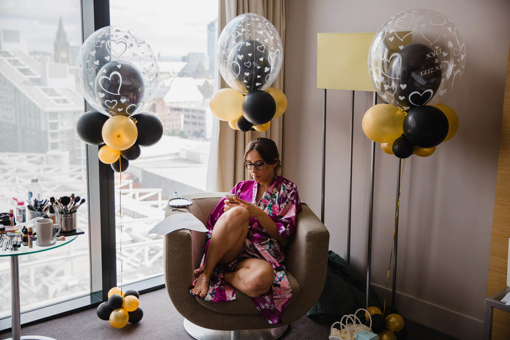 bridesmaid sat on chair looking at phone surrounded by gold and black balloons next to hotel window