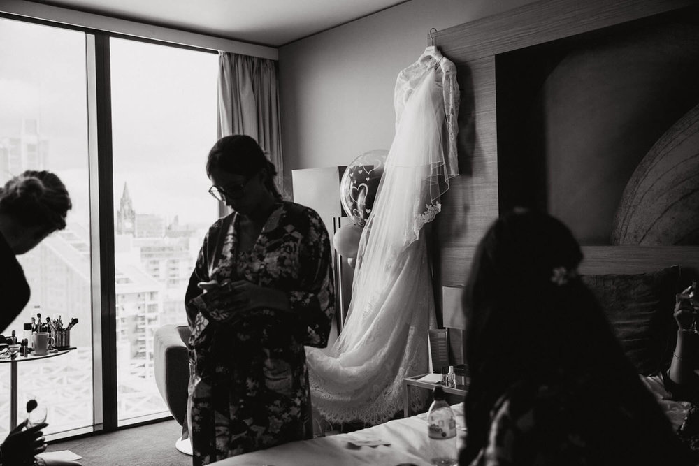 black and white photograph of pronovias wedding dress hung up on wall in focus with bridesmaids in foreground blurred