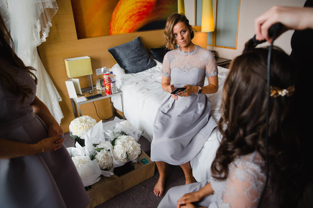 Bridesmaid sat on end of bed talking to the rest of the bridal party