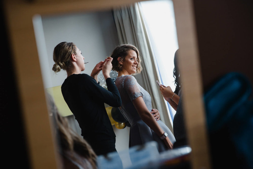 photograph taken in the mirror showing bridesmaid having her make up done by the hotel window