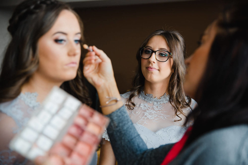 bridesmaid looks on as flower girl has make up done