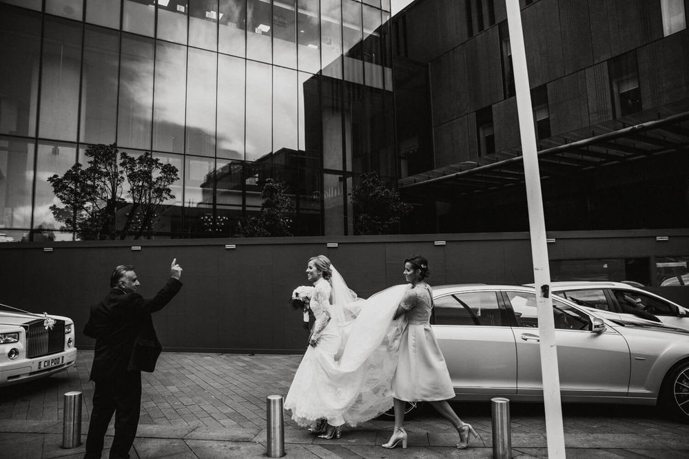 black and white side on photograph of bridesmaid carrying brides dress out to the wedding car in front of hilton hotel beetham tower