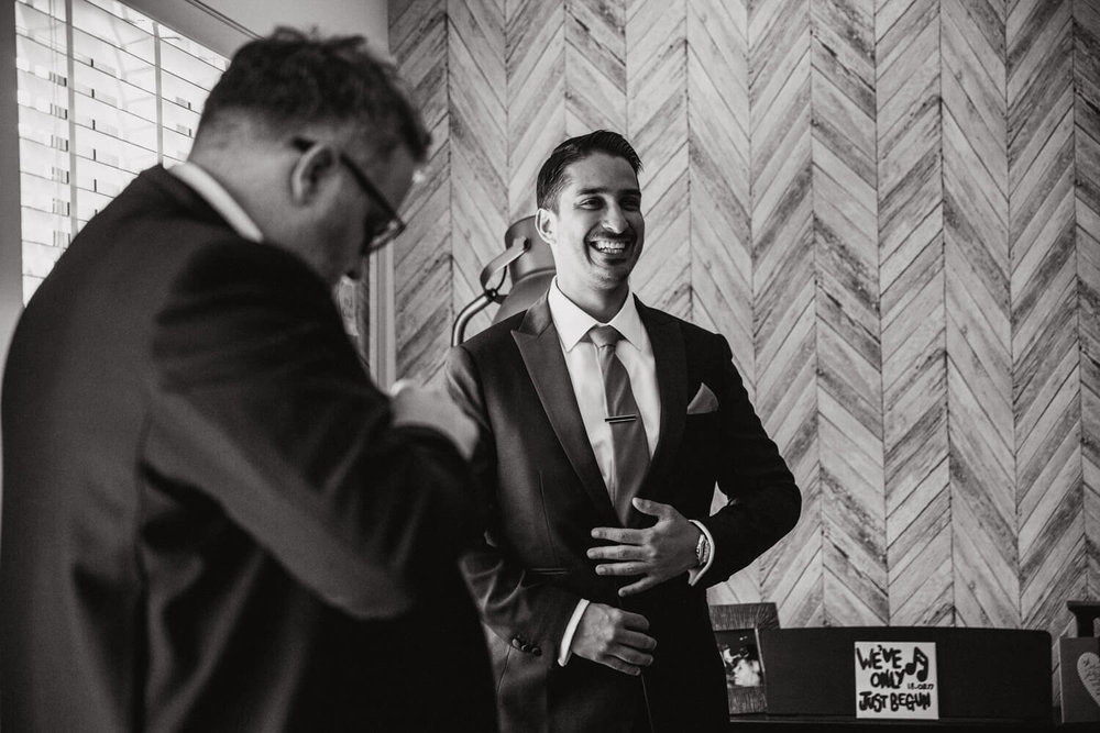 smartly dressed usher of groom fixes his cufflink while laughing with groomsmen
