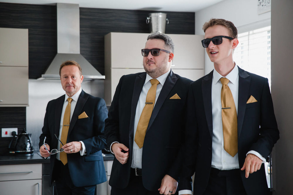 groomsmen wearing sunglasses in the kitchen all in suits and yellow ties