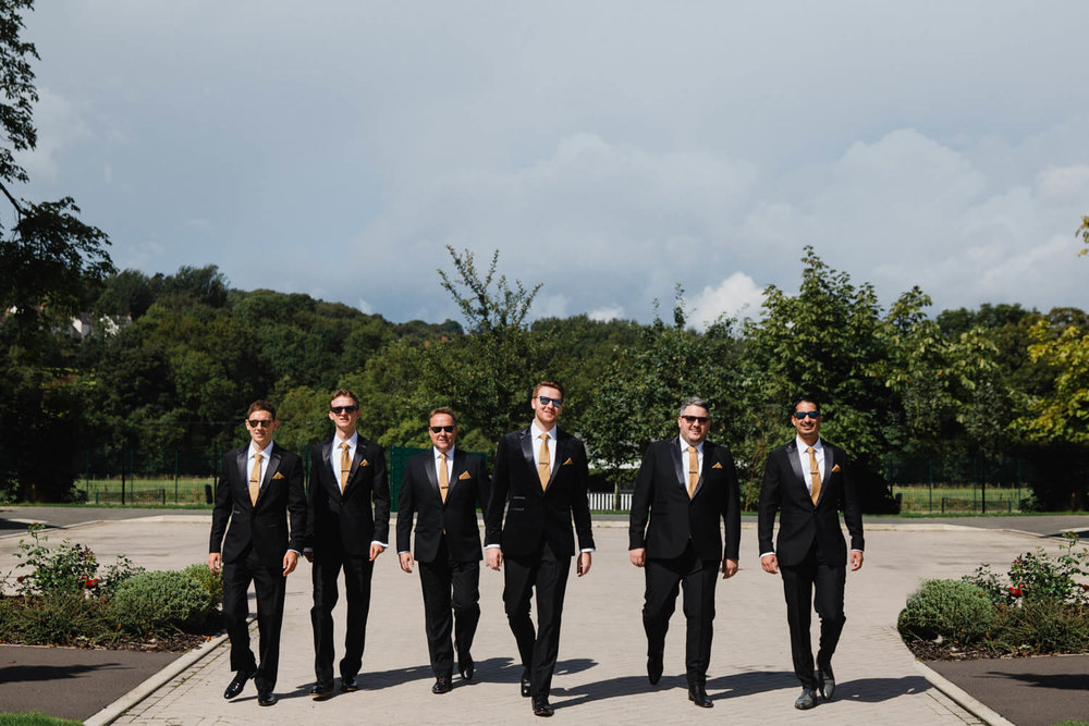 groomsmen all suited and ready to go walking down the road to the ceremony venue