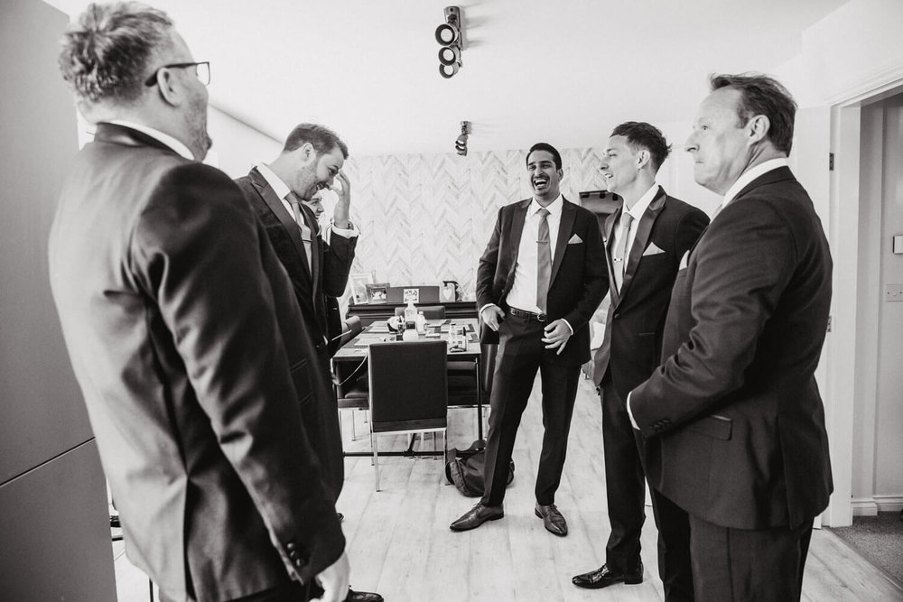 wide angle photograph of groom and friends in living room laughing and joking before the wedding
