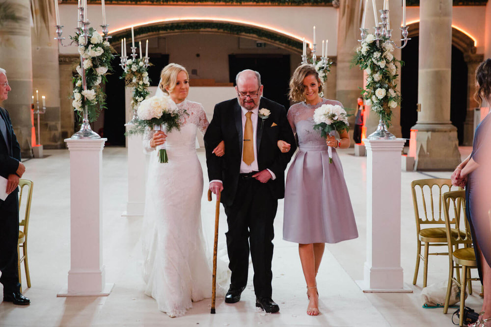 bride walking down the aisle holding bouquet with father and maid of honour alongside