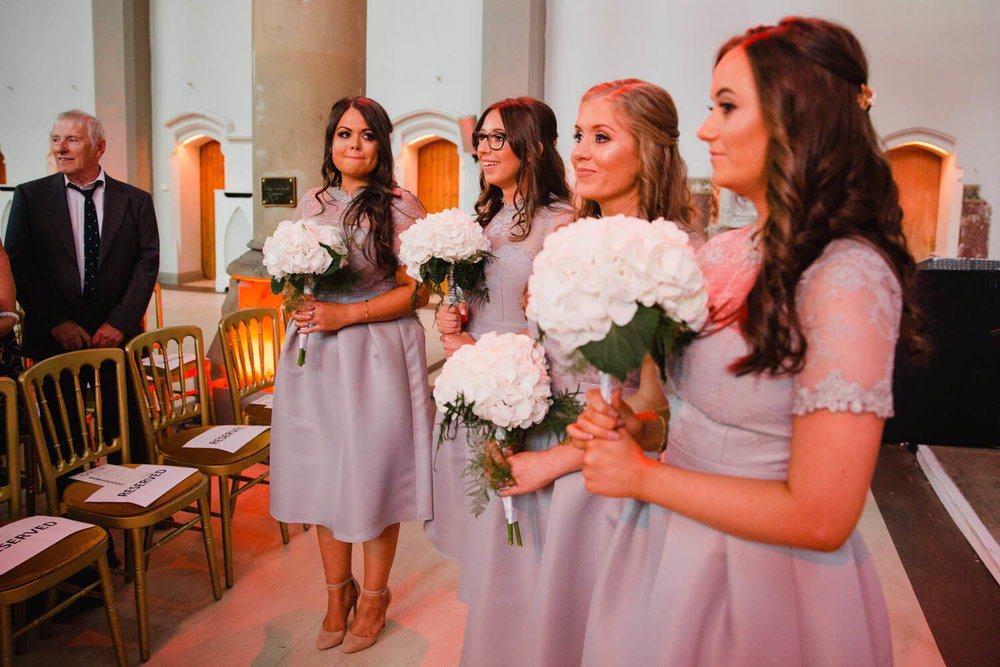bridesmaids holding bouquets at the top of the aisle of the abbey ceremony