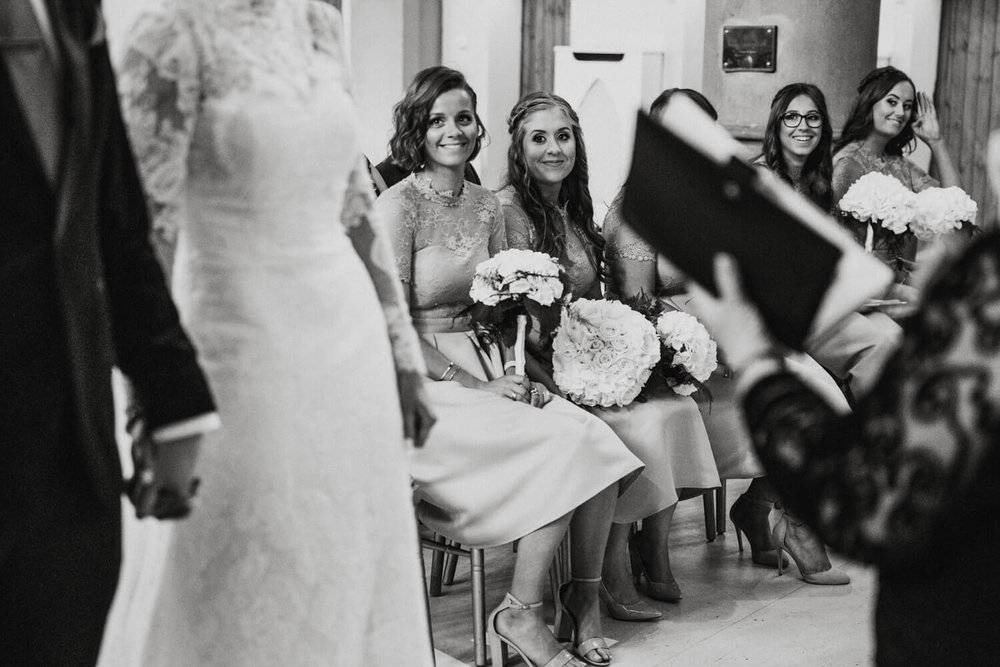 black and white photograph of bridesmaids looking on at ceremony