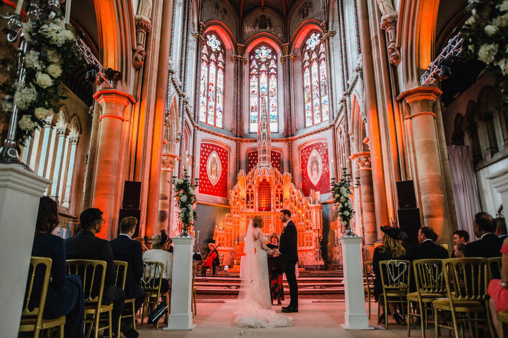 wide angle photograph of wedding rings being exchanged with stained glass window backdrop above the abbey alter