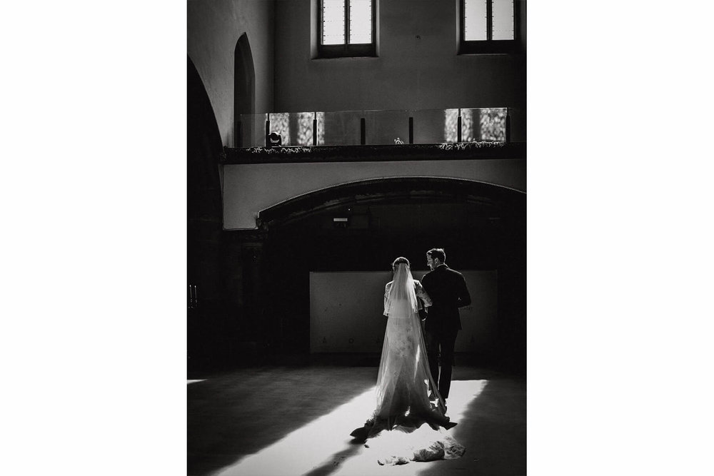 black and white photograph of bride and groom stood facing away from camera with veil lit up in window light