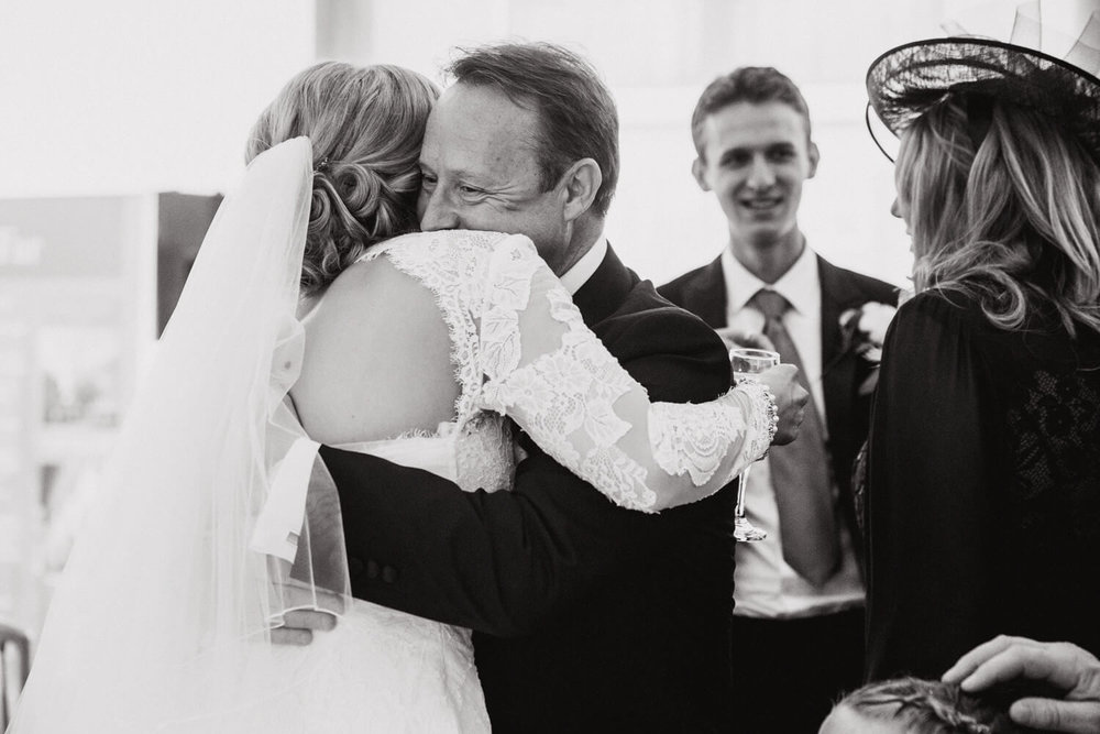 black and white photograph of father of groom sharing intimate hug with bride after service