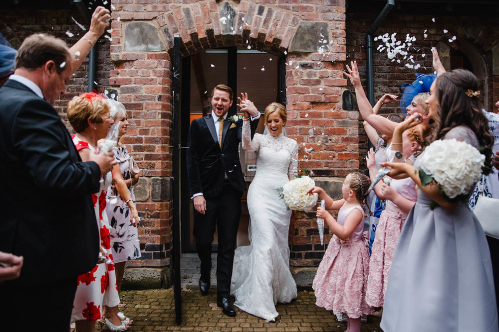 newlyweds walking through confetti being thrown by wedding party in the priory