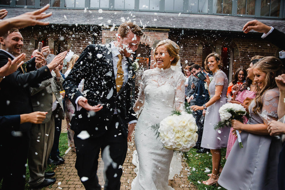 groom receiving a large dose of confetti to the face during the celebrations in the priory