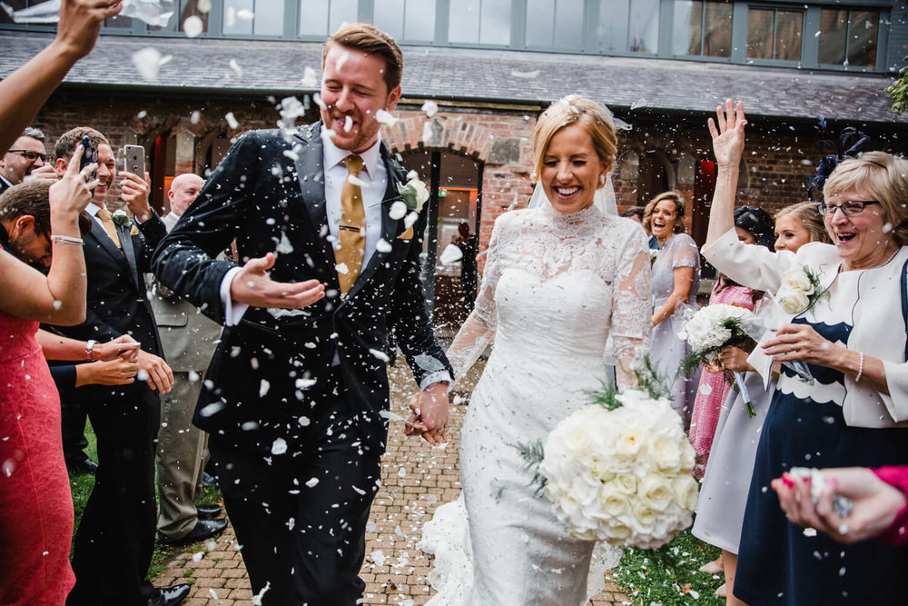newly wedded couple laughing while walking through confetti thrown by guests and family