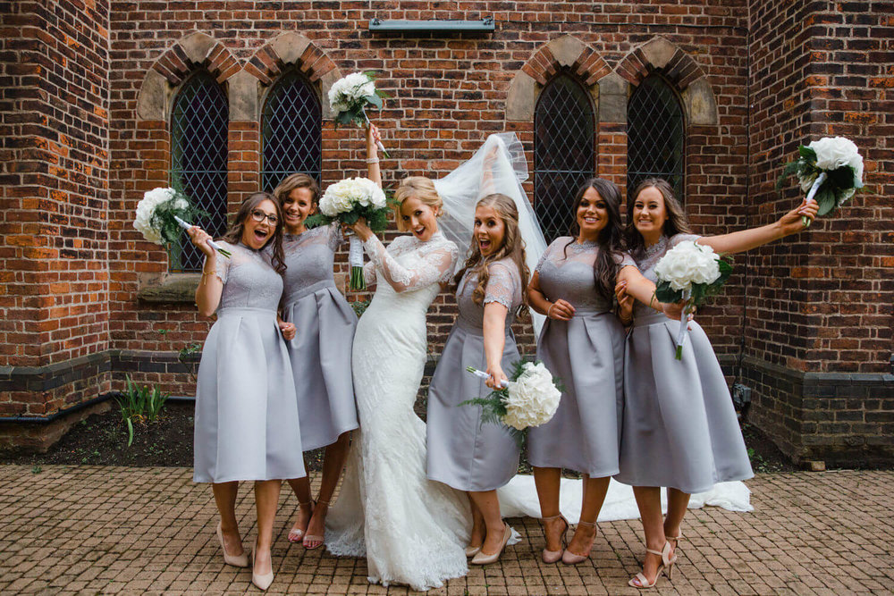 bride and bridesmaids holding bouquets and posing for the camera