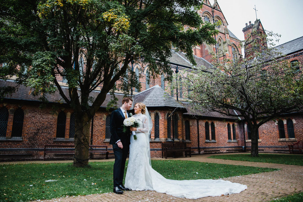 wide angle photograph of bride and groom showing full length veil at gorton monastery