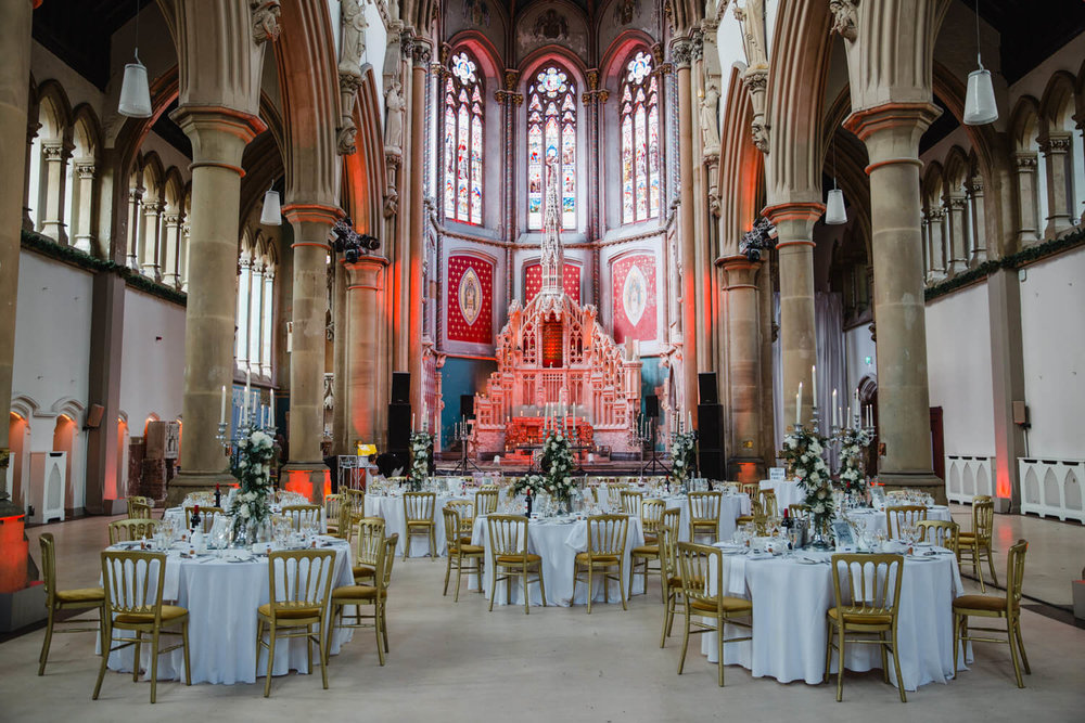 wide angle photograph of the grand hall lined with cloisters and wedding breakfast tables set up for meal and speeches