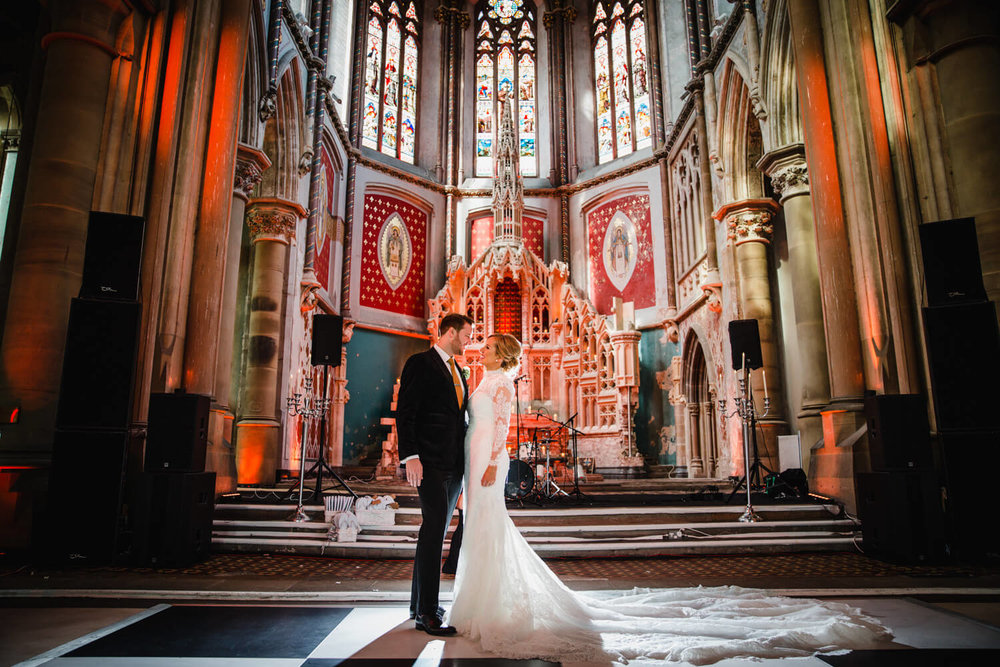 newly married couple posing at top of aisle in front of stained glass windows and gorton monastery architecture