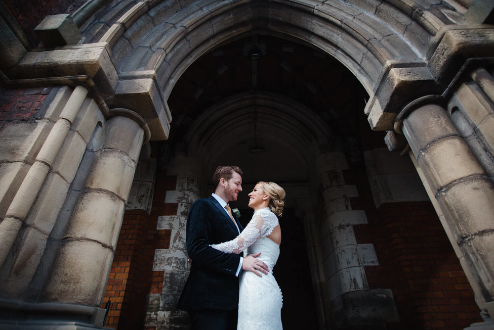 close up of bride and groom holding each other under cloisters
