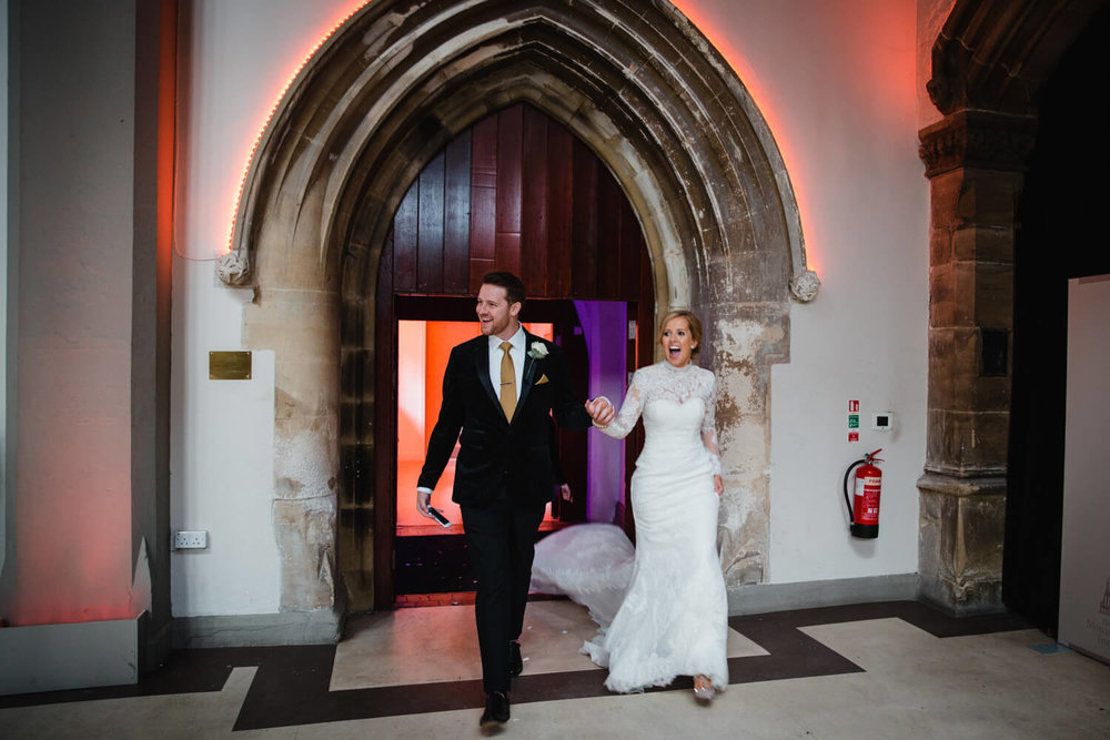 bride and groom entering the main hall for the wedding breakfast meal to begin