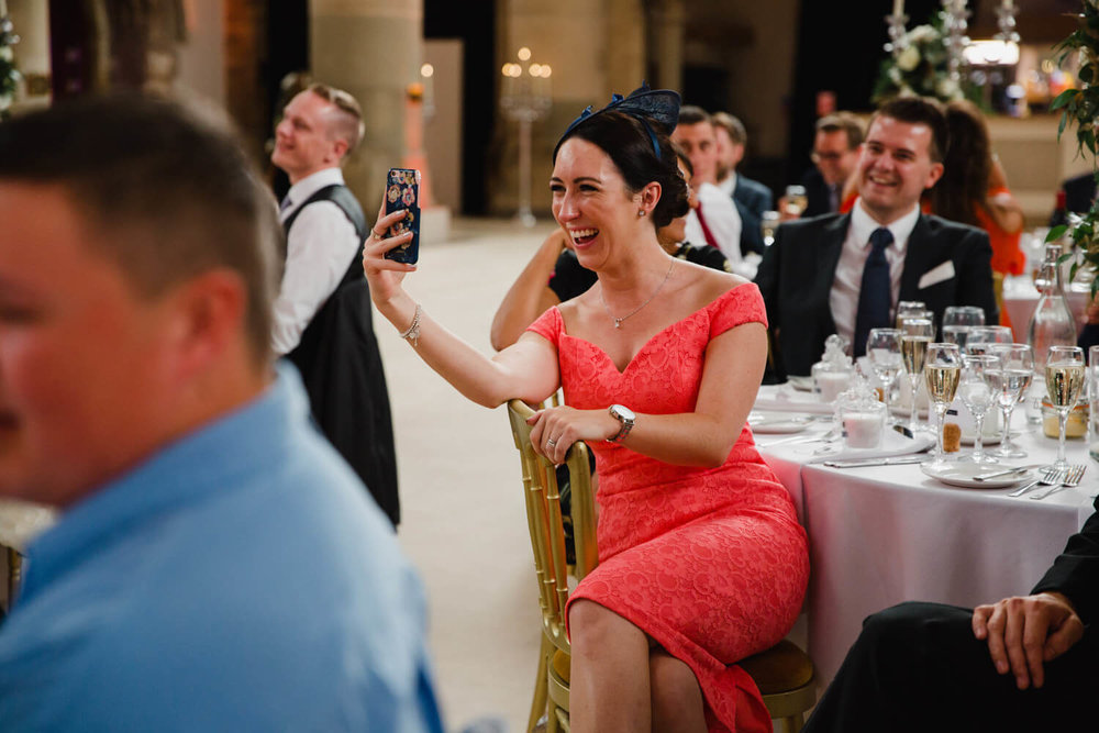 wedding party guest recording grooms speech on camera phone while laughing
