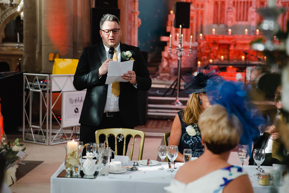 long range photograph of best man delivering his speech to wedding party