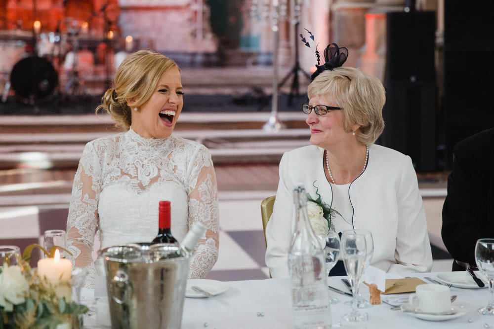 bride laughing with mother sat at top table during speeches