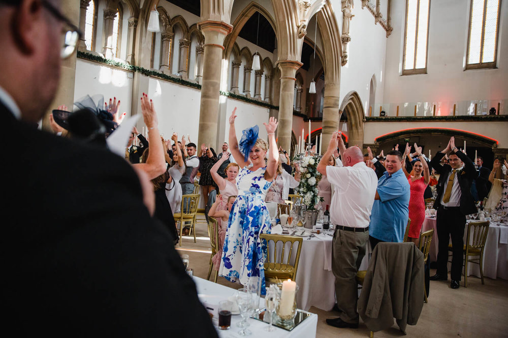 wedding party with arms in air as part of the best man speech celebrations