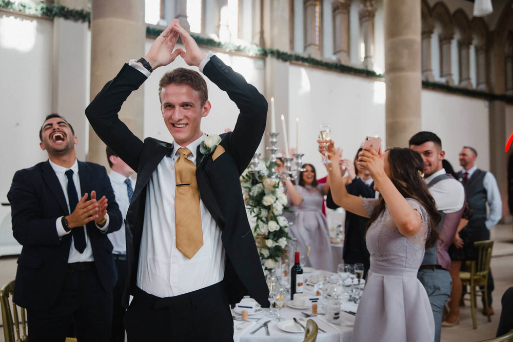 wedding guest with arms in the air while other guests are out of focus in background laughing
