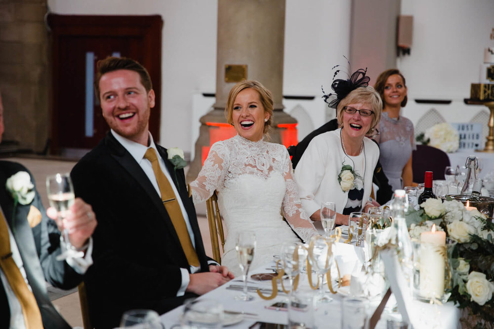 top table of wedding party laughing at best man speech