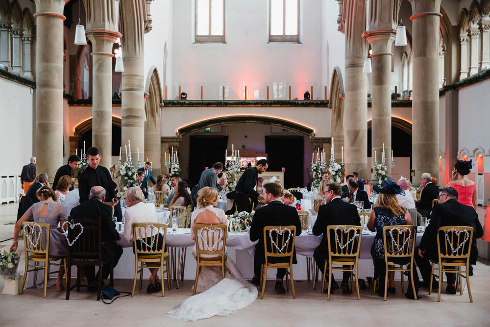 photograph taken from behind top table with bride groom and families all sat in love heart chairs