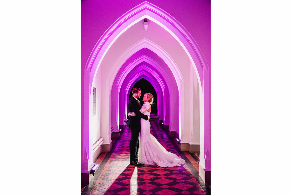 back lit portrait of bride and groom at gorton monastery under pink light cloister archway