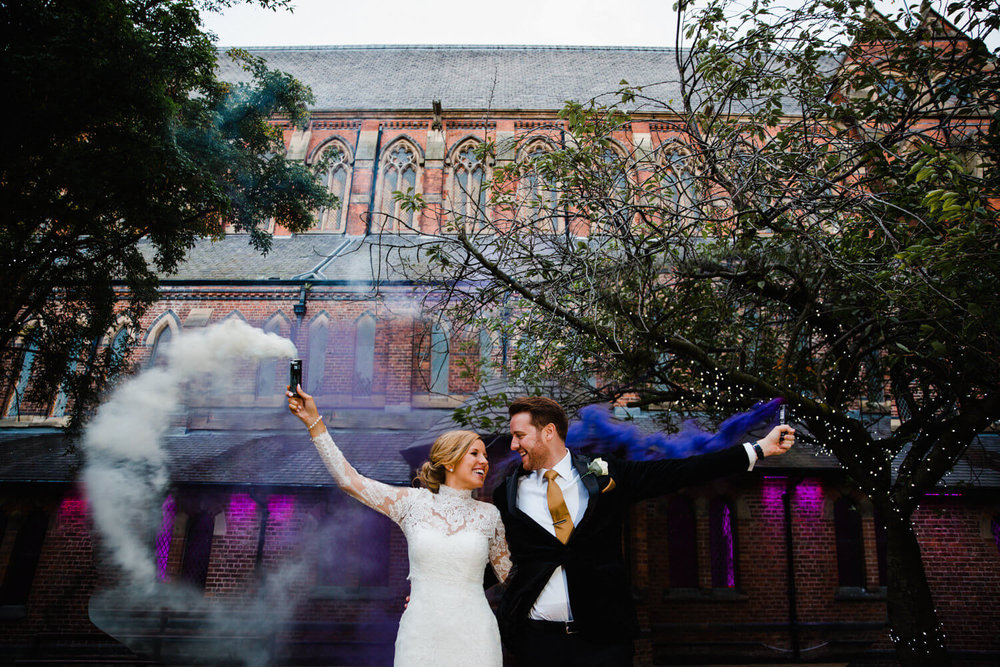 bride and groom in courtyard at gorton monastery holding purple and white smoke grenades in the air