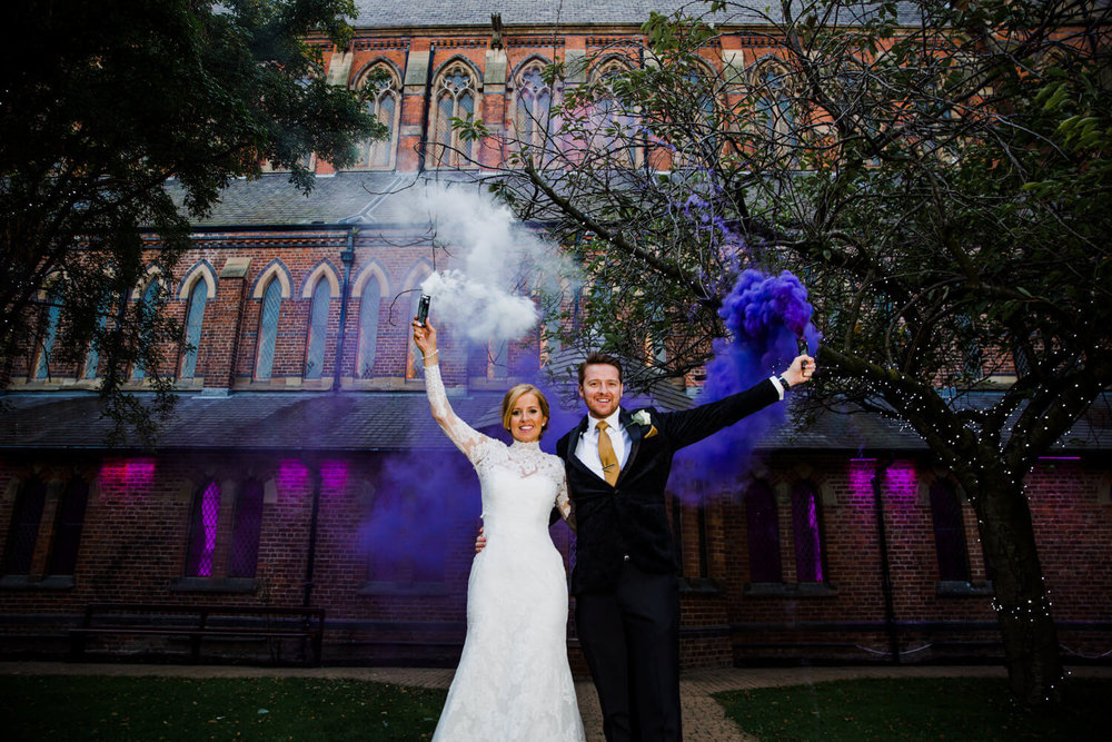 smoke grenade portrait of newly wedded couple in courtyard at gorton monastery