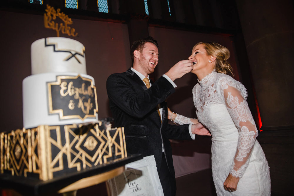 groom feeding bride great gatsby themed wedding cake