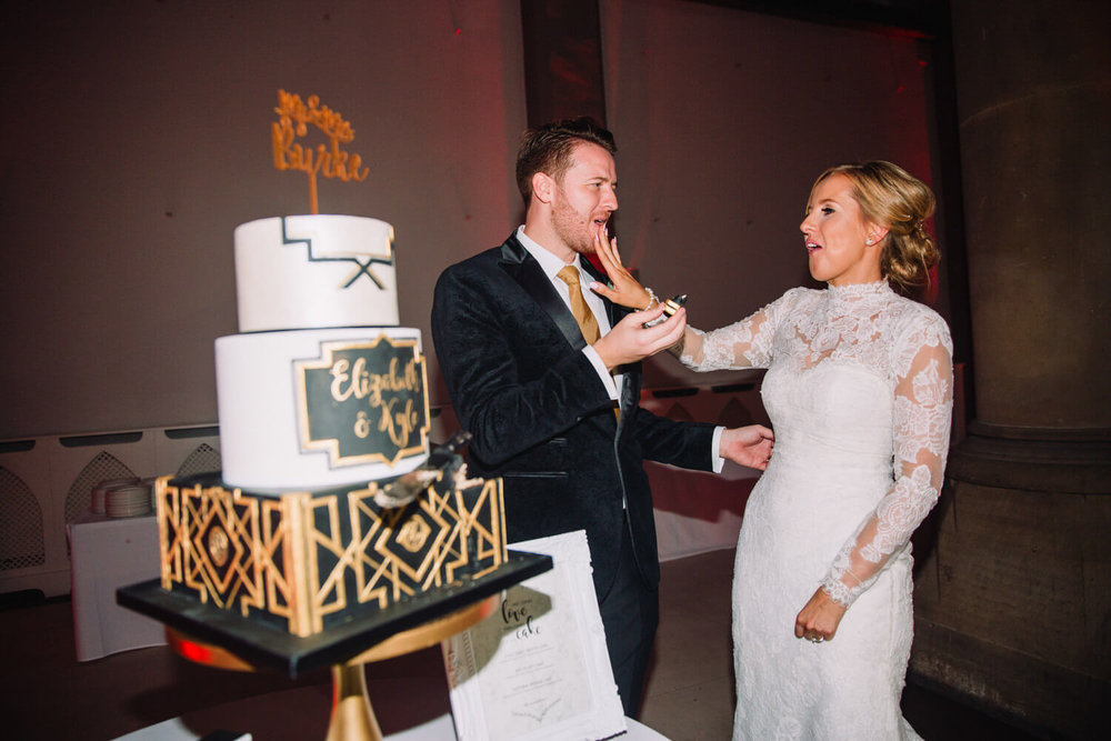 bride smearing wedding cake over grooms mouth while feeding it to him