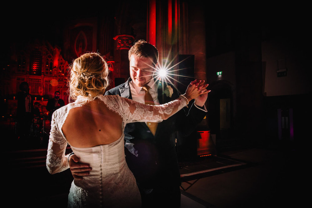 bride turned with back to camera and flashes giving aperture stars during first dance