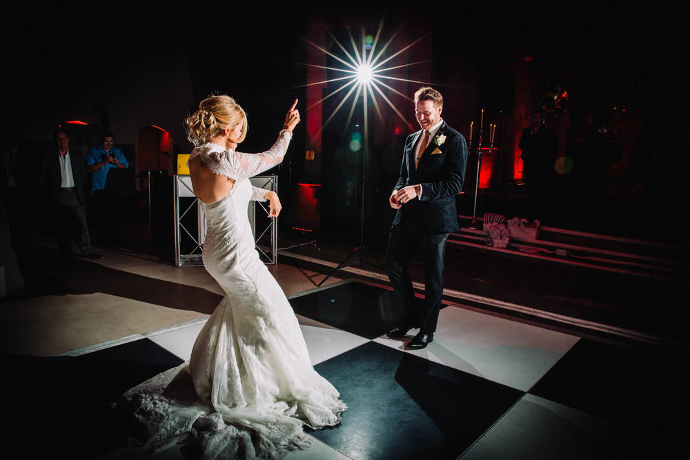 bride pointing at groom for dancing at first dance in front of all friends and family